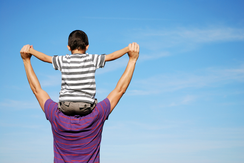 A child is sitting on the fathers shoulders who is carrying him around outdoors in the blue sky